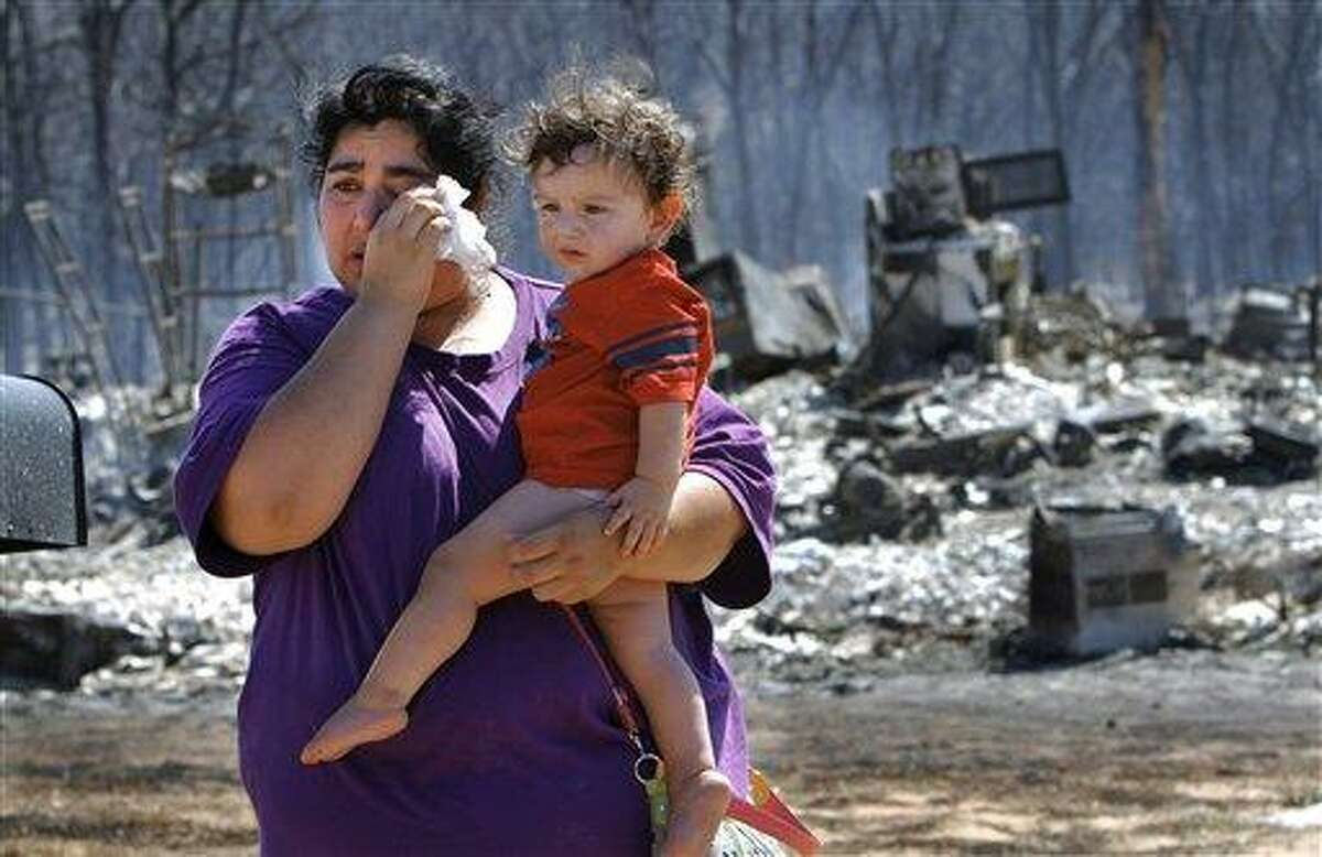 Victoria Landavazo holds youngest child, Axel, 1 year old, while wiping tears after arriving Saturday with other members of her family to see for the first time what the wildfire had done to their home in Luther, Okla. While residents of one Oklahoma town sifted through their charred belongings Saturday to salvage what they could after a roaring wildfire that may have been deliberately set, residents in two other towns were being ordered to evacuate their homes. The fire near Luther, which is about 25 miles northeast of Oklahoma City, destroyed nearly five dozen homes and other buildings before firefighters were able to gain some measure of control Saturday. Associated Press