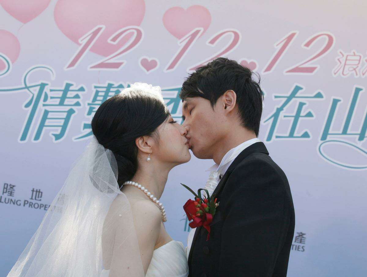 A couple kiss during a mass wedding ceremony at the Peak in Hong Kong, Wednesday, Dec. 12, 2012. At least 700 couples are expected to get married in the date 12/12/12, the last such triple-date in this year in Hong Kong as they believe the date will bring them everlasting love. (AP Photo/Kin Cheung)