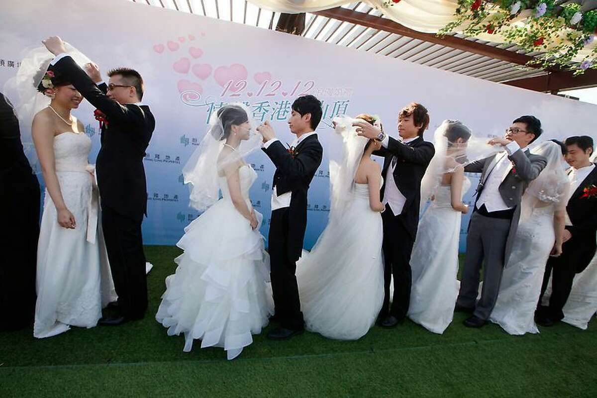 Twelve couples attend a mass wedding ceremony at the Peak in Hong Kong, Wednesday, Dec. 12, 2012. At least 700 couples are expected to get married in the date 12/12/12, the last such triple-date in this year in Hong Kong as they believe the date will bring them everlasting love. (AP Photo/Kin Cheung)
