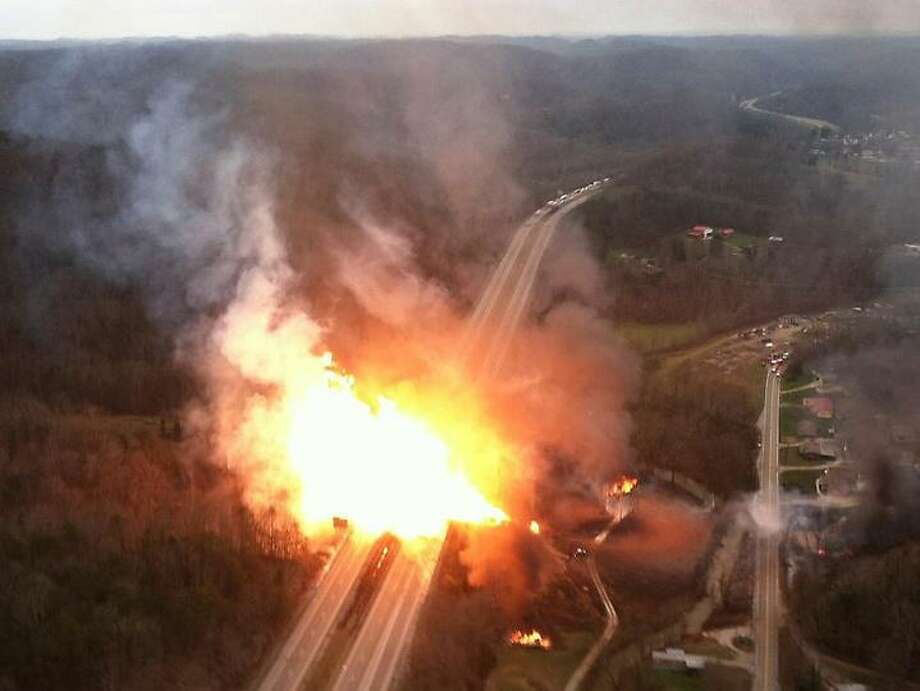 This image provided by the West Virginia State Police shows a fireball erupting across Interstate 77 from a gas line explosion in Sissonville, W. Va.,Tuesday Dec. 11, 2012. At least five homes went up in flames Tuesday afternoon and a badly damaged section of Interstate 77 was shut down in both directions near Sissonville after a natural gas explosion triggered an hour-long inferno that officials say spanned about a quarter-mile.  (AP Photo/West Virginia State Police) Photo: ASSOCIATED PRESS / AP2012