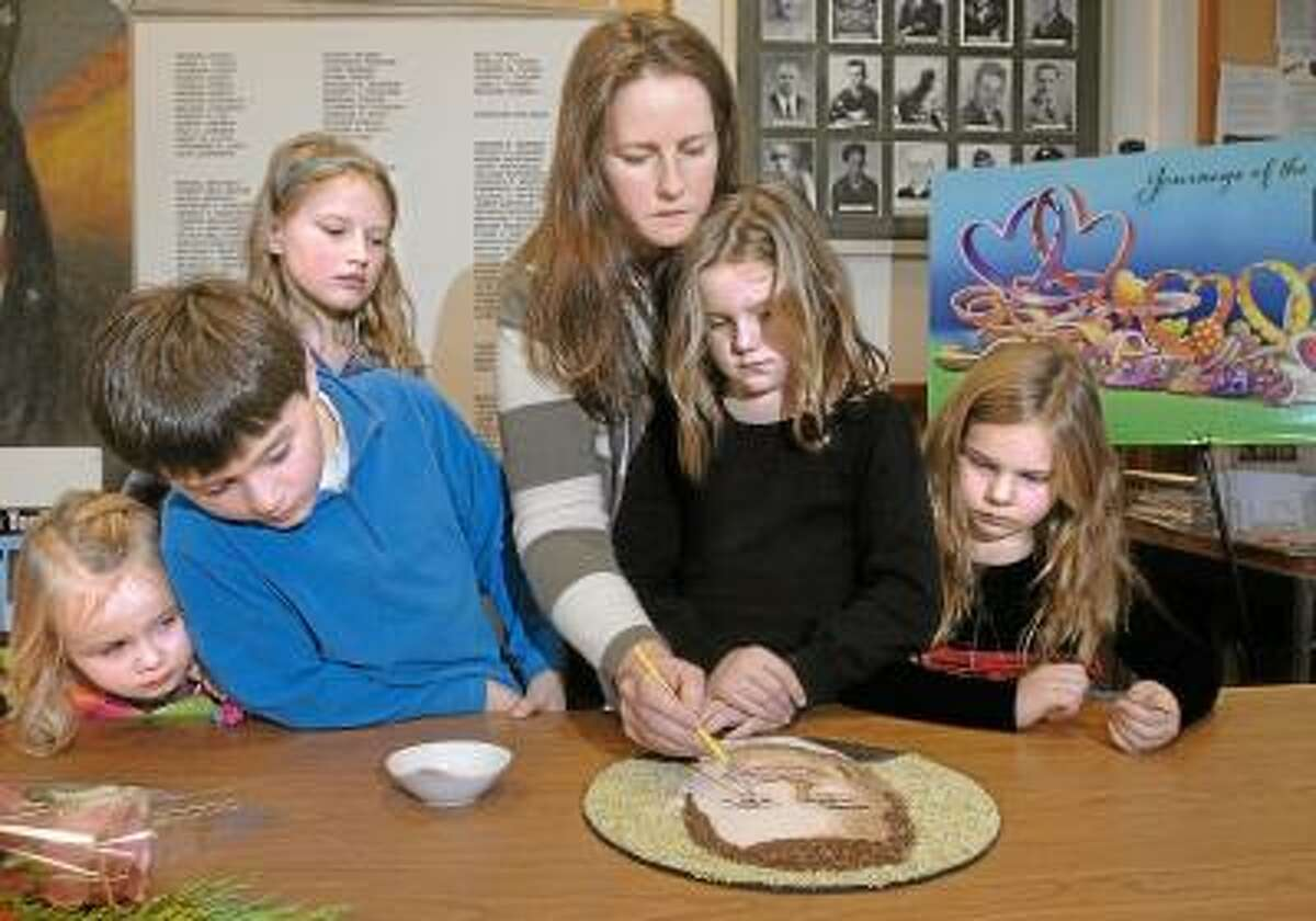 Catherine Avalone/The Middletown Press Deep River resident Sage Novak applies the finishing touch to the floragraph of her deceased husband, Rob Novak, as her two daughters Grace, 9, and Natalie, 6, and their cousins Abby Shakun, 9, Patrick Shakun, 8, and Madilyn Novak, 3, wait for their turn at a ceremony held at the Deep River Town Hall Wednesday afternoon. The floragraph portrait will be one of 72 portraits displayed on the The Donate Life float