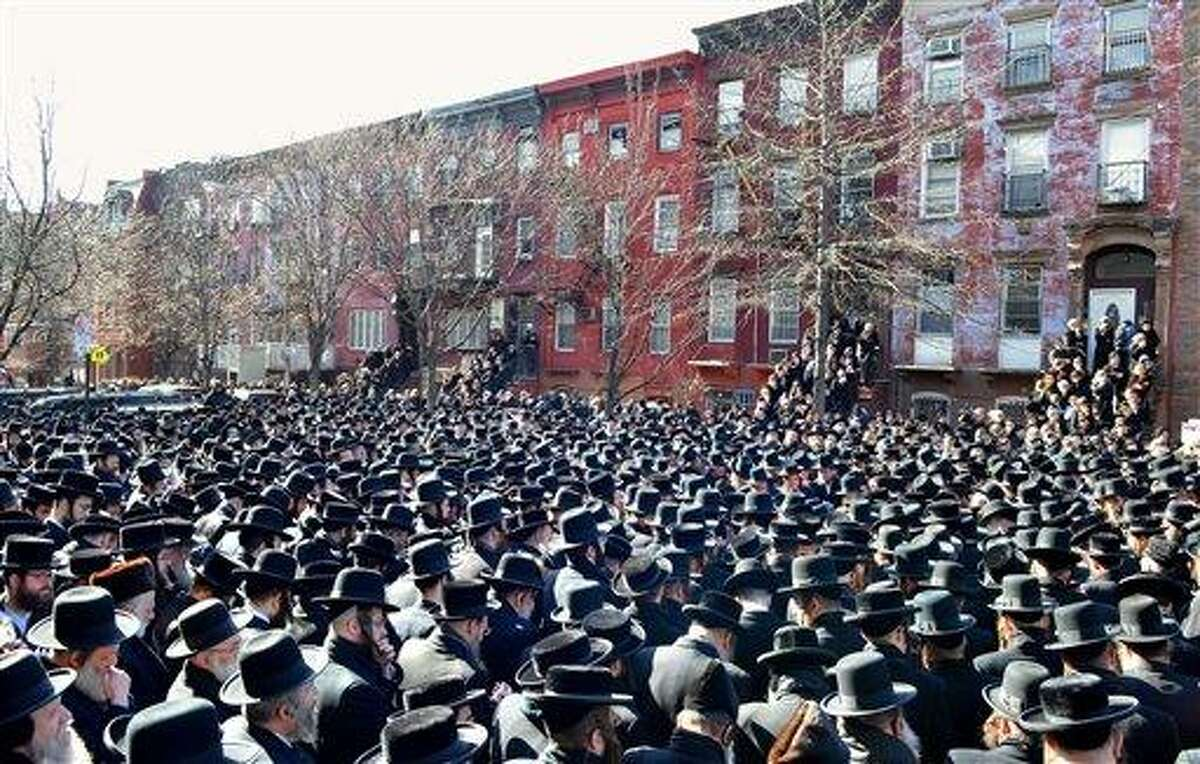 In this March 3, 2013, photo provided by VosIzNeias.com, Orthodox Jewish mourners gather outside the Congregation Yetev Lev D'Satmar synagogue in Brooklyn's Williamsburg neighborhood for the funeral of two expectant parents who were killed in a car accident early Sunday, in New York. The baby of Nachman and Raizy Glauber, a boy, was delivered prematurely by cesarean section and survived until the next morning, but died around 5:30 a.m. on Monday, March 4. Police were searching for the driver of a BMW and a passenger who fled on foot after slamming into the livery cab that was transporting the 21-year-old couple to a hospital. (AP Photo/VosIzNeias.com, Eli Wohl)