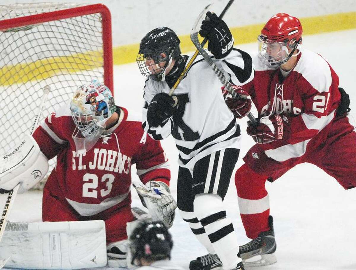 Catherine Avalone/The Middletown Press Xavier junior forward Colin Beaudoin and goalie Mario Pizzeri and Matt Pieciak St. John's-Shrewsbury look for the puck Wednesday evening at the Spurrier-Snyder Rink at Wesleyan University . St. John's won 3-1.