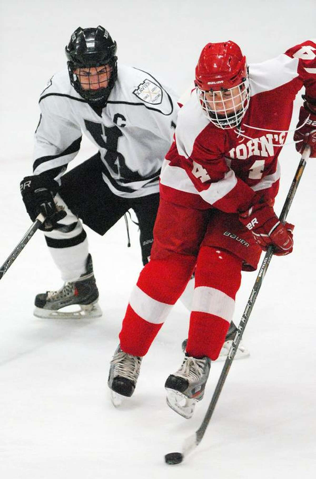 Catherine Avalone/The Middletown Press Xavier senior co-captain Dan Dupont defends Hunter Burdick of St. John's-Shrewsbury, Mass. Wednesday evening at Wesleyan's Spurrier-Snyder Rink. The Pioneers defeated the Falcons 3-1.