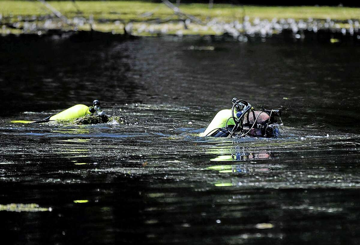 Members of the Connecticut State Police Dive Team searches Pine Lake in Bristol, Conn., on Tuesday, Aug. 6, 2013, the hometown of the former New England Patriots football player Aaron Hernandez. The divers searched the lake for a second week. Hernandez has pleaded not guilty to murder in the death of Odin Lloyd, a 27-year-old Boston semi-professional football player. (AP Photo/Bristol Press, Mike Orazzi)