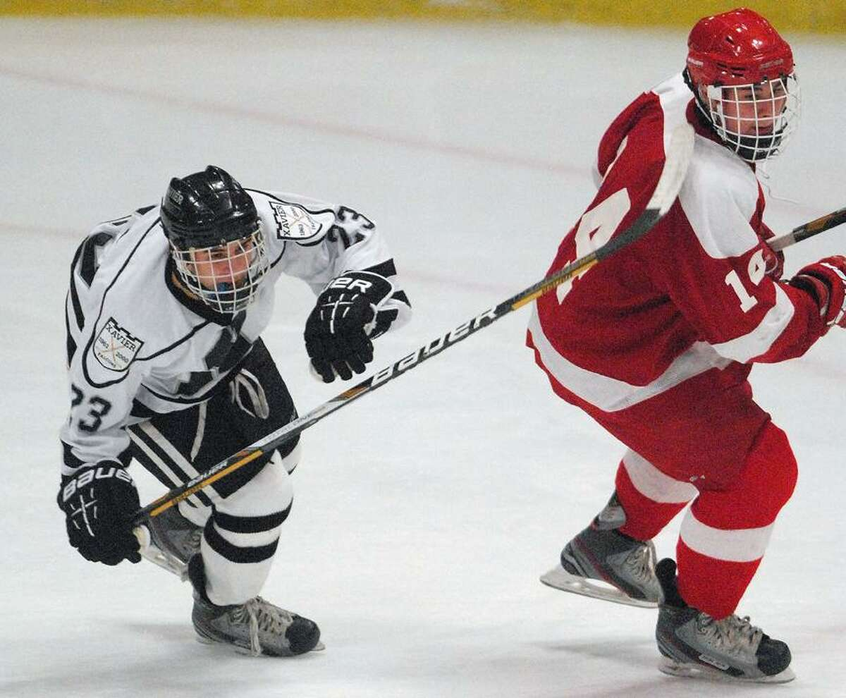 Catherine Avalone/The Middletown Press Xavier senior forward Ryan McLellan battles with Chris Coveney of St. John's-Shrewsbury, Mass. Wednesday evening at Wesleyan's Spurrier-Snyder Rink. The Pioneers defeated the Falcons 3-1.