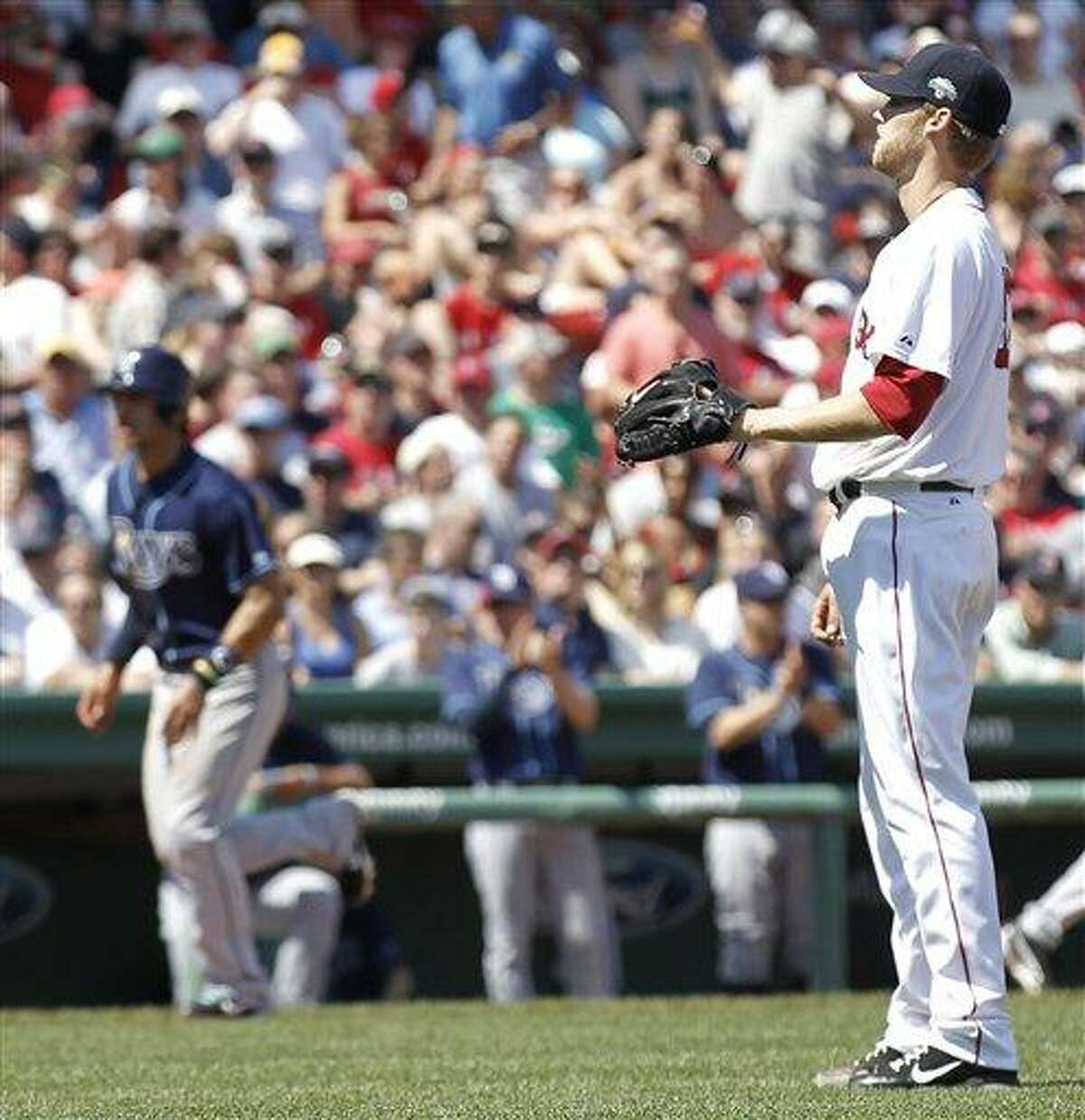 Boston Red Sox starting pitcher Daniel Bard waits to get the ball back as Tampa Bay Rays' Sean Rodriguez, left, walks home to score the only run of the game during the seventh inning of Tampa Bay's 1-0 win in a baseball game at Fenway Park in Boston Monday, April 16, 2012. (AP Photo/Winslow Townson)