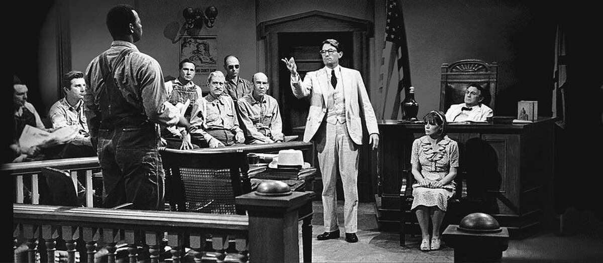 """""""Defense lawyer Atticus Finch (Gregory Peck), center, defends Tom Robinson (Brock Peters), left, against the false rape accusation of Mayella Ewell (Collin Wilcox), right."""" (NBC Universal)"""