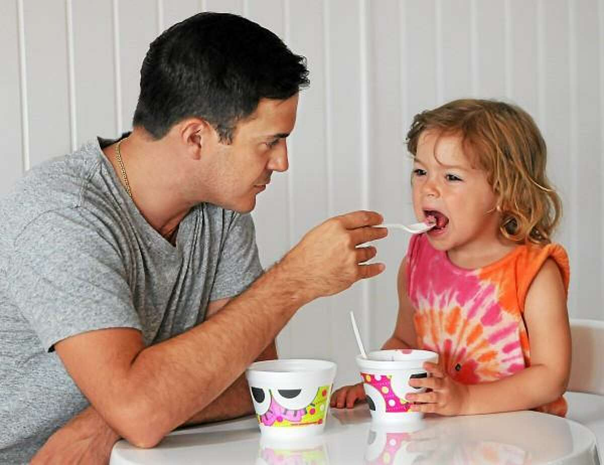 Catherine Avalone - The Middletown Press Cromwell resident Joe Cardella shares a spoonful of frozen yogurt with his 3-year old daughter Madeline at Sweet Frog Frozen Yogurt at 34 Shunpike Road in Cromwell early Wednesday evening.