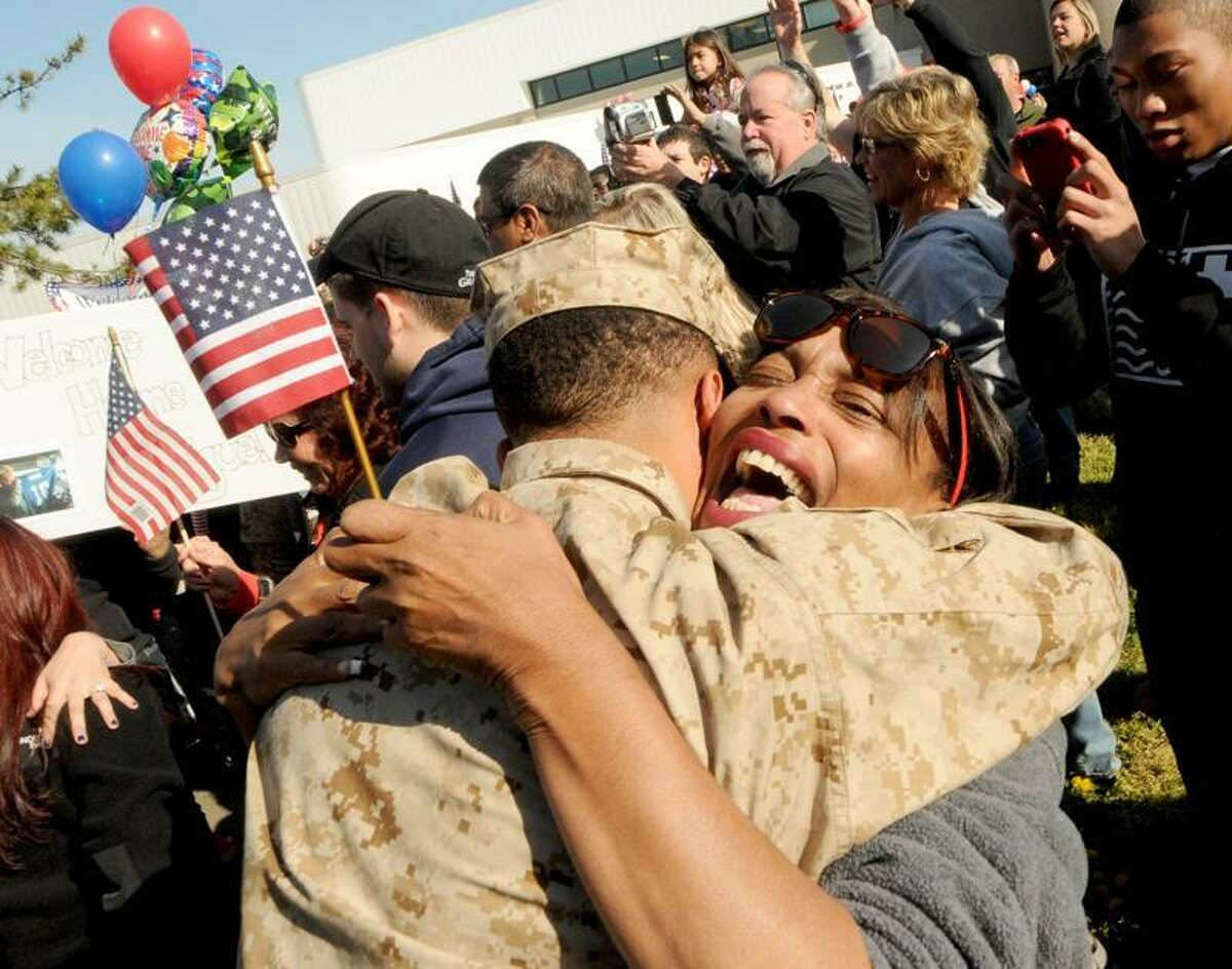 USMC Corporal Treyvon Briggs of Bridgeport is hugged by his mother Gretchen Autry of Bridgeport as she welcomes her son back home as 31 United States Marine Corps reservists of the 6th Motor Transport Battalion return from their deployment in Afghanistan back to the Marine Reserve Center in New Haven Saturday morning 4/14/12 to family, friends, well-wishers and fellow Marines waiting to greet them. The 6th Motor Transport Battalion is a reserve battalion under the command of the 4th Marine Logistics Group. Photograph by Peter Hvizdak / New Haven Register