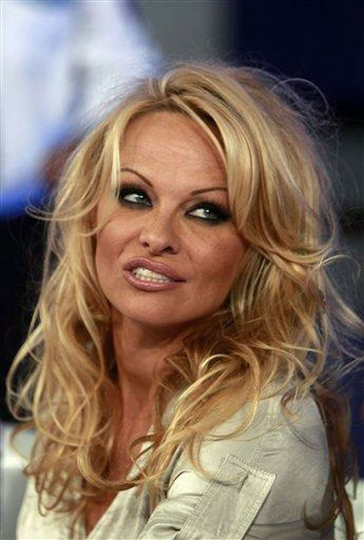 """FILE - In this Sept. 25, 2011 file photo, Canada's actress Pamela Anderson looks on during a news conference after taking part in the Mexican reality show """"La Academia"""" at Azteca TV studios in Mexico City. Anderson and Lionel Richie owe the government money. California tax authorities have put Anderson on the latest list of the state's biggest income-tax delinquents. The Franchise Tax Board said the former """"Baywatch"""" star owes $524,241 in state income taxes. Meanwhile, E! Online reports that Richie, a music legend, owes the federal government $1.1 million in unpaid taxes and that a lien has been issued warning that the singers' assets may be seized if he doesn't pay up in a timely manner. (AP Photo/Moises Castillo, File)"""