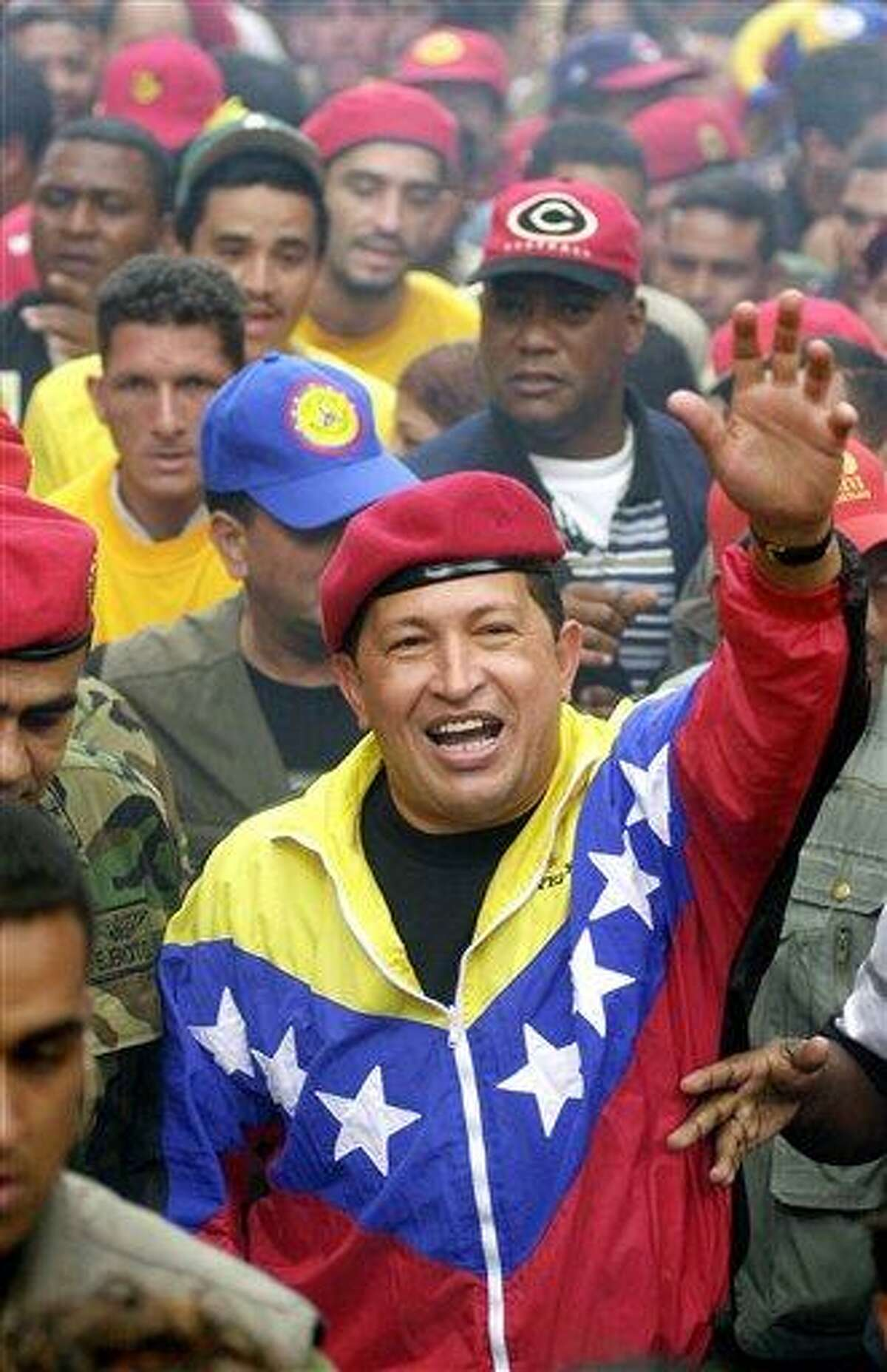 FILE - In this Jan. 23, 2002 file photo, Venezuela's President Hugo Chavez waves to supporters during a government march commemorating the anniversary of Venezuelan democracy in Caracas, Venezuela. Venezuela's Vice President Nicolas Maduro announced on Tuesday, March 5, 2013 that Chavez has died. Chavez, 58, was first diagnosed with cancer in June 2011. (AP Photo/Fernando Llano, File)