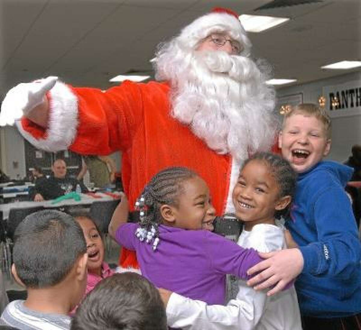 """Cromwell residents Talia Jones, 6, her twin brother Tarrell Jones and Brandon Stefurak, 11 greet Santa on his arrival at the 28th Annual Santa's Workshop hosted by Cromwell Youth Services and Cromwell High School's Student Council Monday evening in the high school cafeteria. Brandon Stefurak shouted, """"Yay, Santa is here!"""" Catherine Avalone/The Middletown Press"""