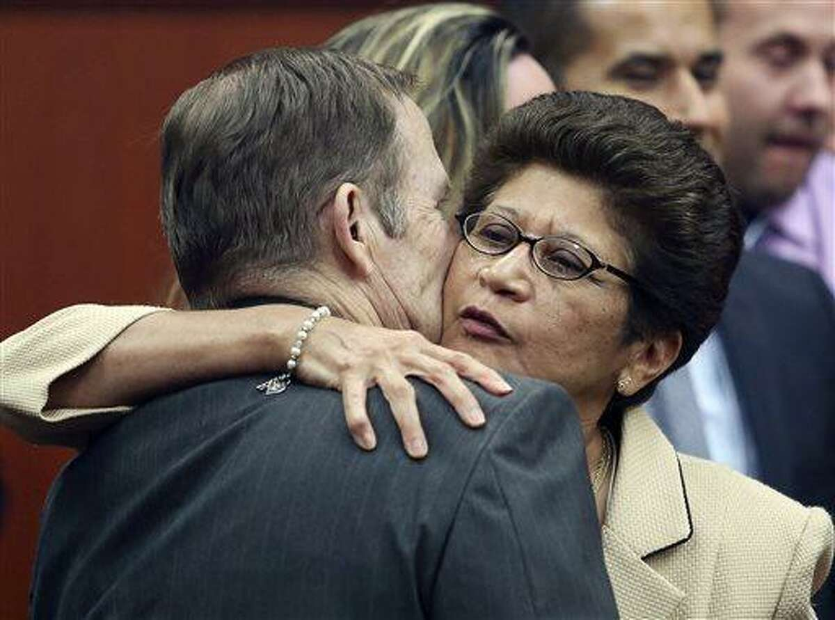 George Zimmerman's parents Robert Zimmerman Sr. and Gladys Zimmerman embrace following George Zimmerman's not guilty verdict in Seminole Circuit Court in Sanford, Fla., on Saturday, July 13, 2013. Jurors found Zimmerman not guilty of second-degree murder in the fatal shooting of unarmed 17-year-old Trayvon Martin in Sanford. The six-member, all-woman jury deliberated for more than 15 hours over two days before reaching their decision Saturday night. (AP Photo/Gary W. Green, Pool)