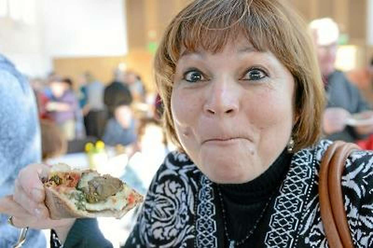 """Dean Marina Melendez bites down on a pizza slice from Mondo at """"A Taste of Middletown"""" sponsored by Wesleyan University's Campus Activities Committee and Human Resources at Beckham Hall Tuesday afternoon. Photo by Olivia Drake/Special to the Press"""