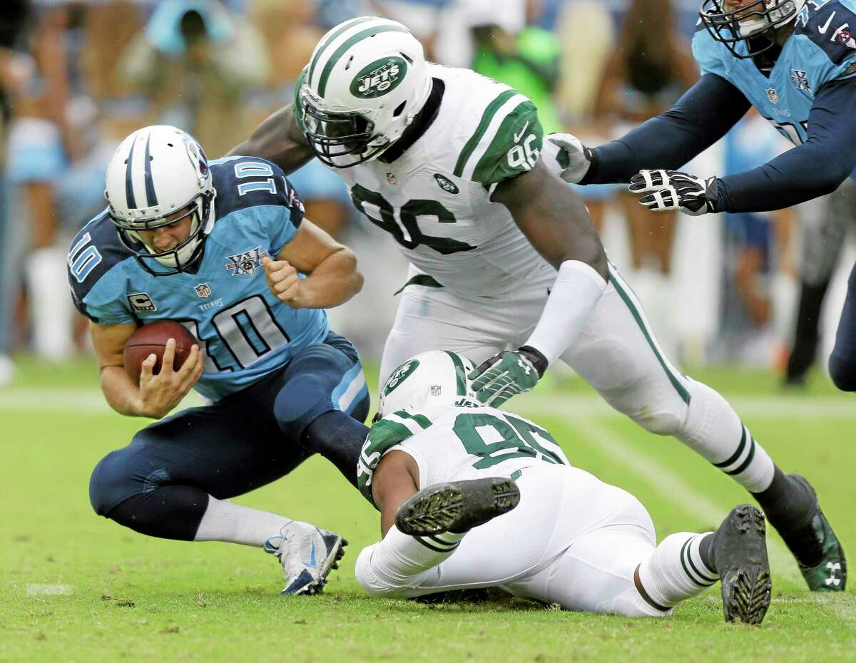 New York Jets defensive end Muhammad Wilkerson (96) and Antwan Barnes bring down Tennessee Titans quarterback Jake Locker in the second quarter of Sunday's game in Nashville, Tenn.