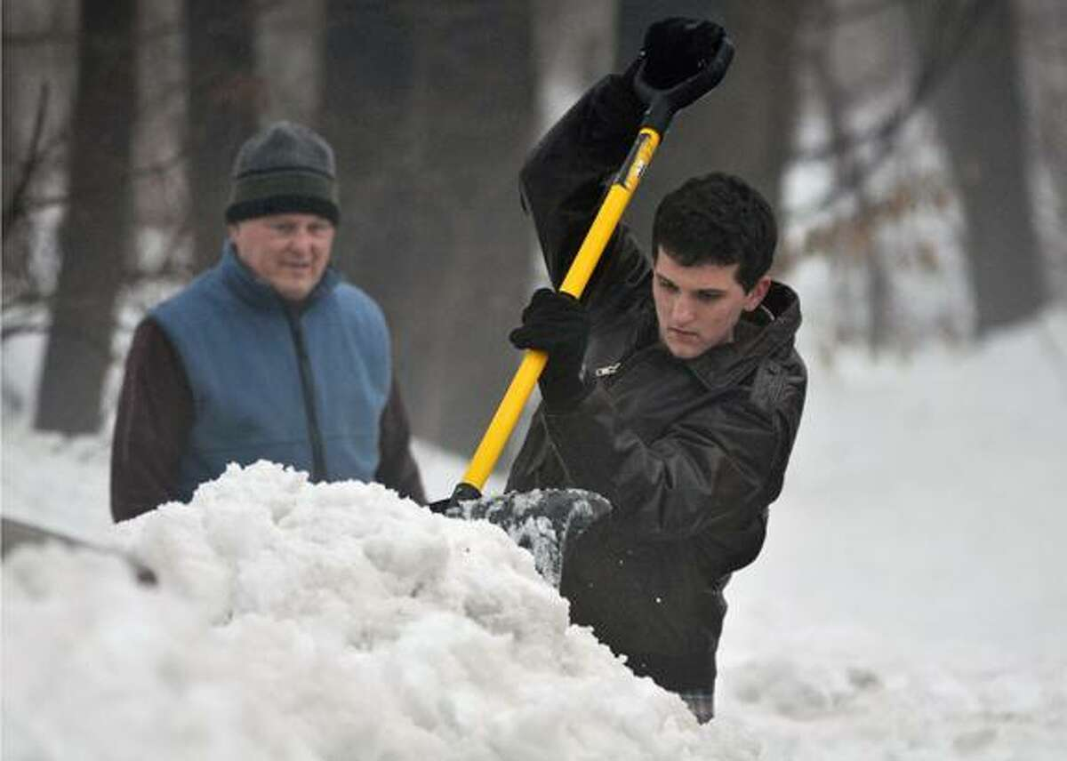 Catherine Avalone/The Middletown PressDurham resident Liam Bialobrzeski, 19 chips away the snow surrounding their mailbox Monday afternoon. Liam's father, John Bialobrzeski, at left, used a snow blower to remove the snow from the area.
