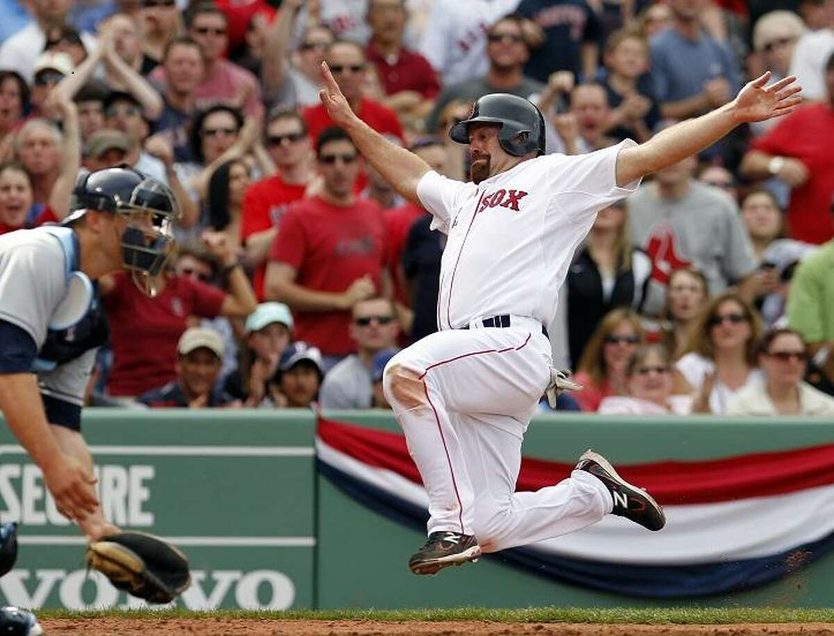 Boston Red Sox's Kevin Youkilis, right, begins to slide safely into home plate as Tampa Bay Rays' Chris Gimenez waits for the throw on a double by David Ortiz in the sixth inning of a baseball game in Boston, Sunday, April 15, 2012. (AP Photo/Michael Dwyer)