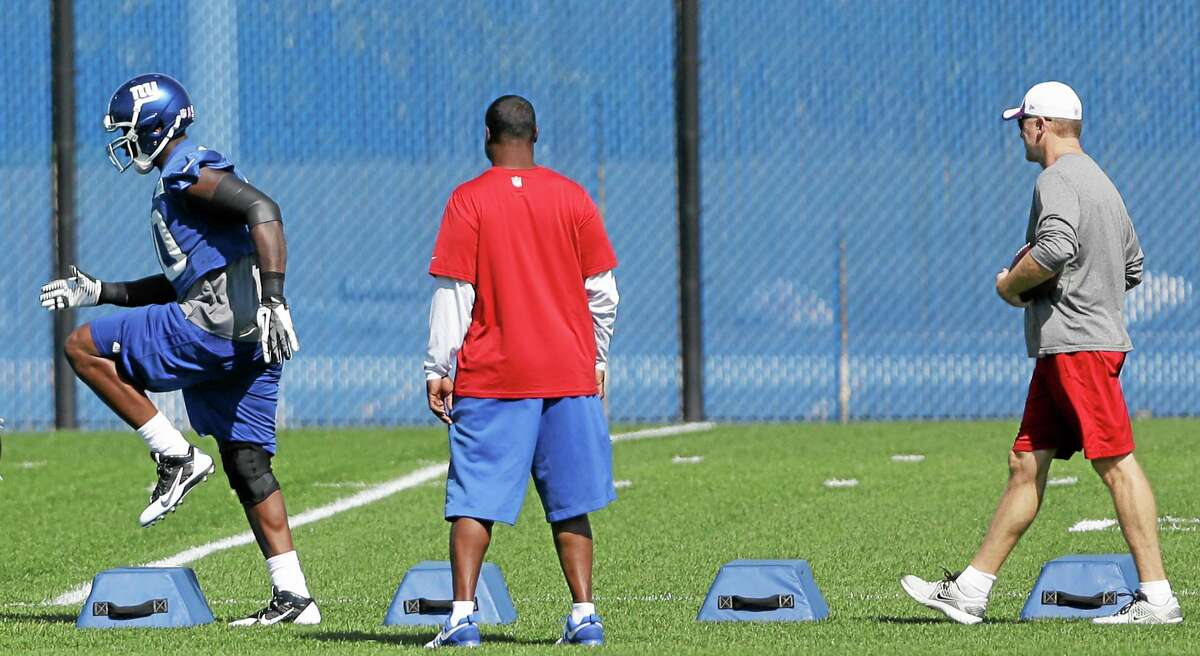 Giants defensive end Jason Pierre-Paul, left, works out during Wednesday's practice in East Rutherford, N.J.