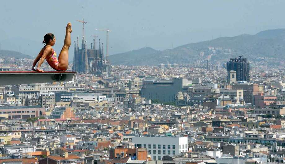 The Sagrada Familia cathedral is seen in the background as an unidentified diver practices ahead of the FINA World Championships in Barcelona, Spain, Monday, July 15, 2013. The FINA swimming World Championships run from July 19 to Aug. 4 in Barcelona. (AP Photo/Manu Fernandez) Photo: ASSOCIATED PRESS / AP2013