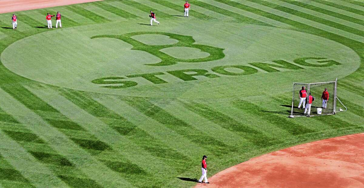 """Red Sox players shag balls Thursday in the outfield during baseball practice, with the """"B Strong"""" logo mowed into the grass in tribute to the Boston Marathon bombing victims, at Fenway Park in Boston. The Red Sox will face the Tampa Bay Rays in Game 1 of the American League division series on Friday in Boston."""