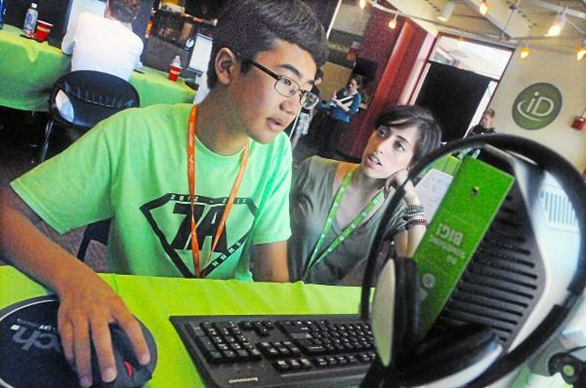 """Catherine Avalone - The Middletown Press Richard Nakatsuka, a rising eighth grader at Woodrow Wilson Middle School works with instructor Veena Vignale, a rising senior at Brown University majoring in computer science at iD Tech Camps at Wesleyan University Tuesday afternoon. The 13-year old Nakatsuka said, """"I can now code programs"""" is working with Vignale learning to create objects for interacting gaming using Java. Students can choose gaming, programming or visual arts."""