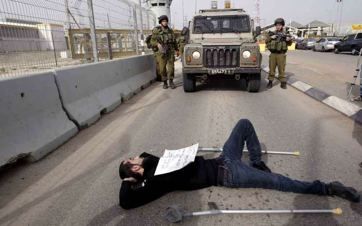 A Palestinian man lays in front of Israeli soldiers during a protest near an Israeli checkpoint in support of the Palestinian prisoners in Israeli jails north of the West Bank city of Jenin , Sunday, March 3, 2013. The fate of the prisoners is sensitive in Palestinian society, where virtually every family has had a member imprisoned by Israel. (AP Photo/Mohammed Ballas)