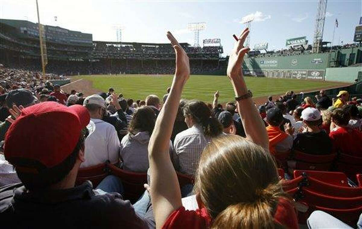 A fan in the bleachers applauds after the Boston Red Sox retired the Tampa Bay Rays in the top of the seventh inning of a baseball game in Boston, Friday, April 13, 2012. The Red Sox won 12-2. (AP Photo/Michael Dwyer)