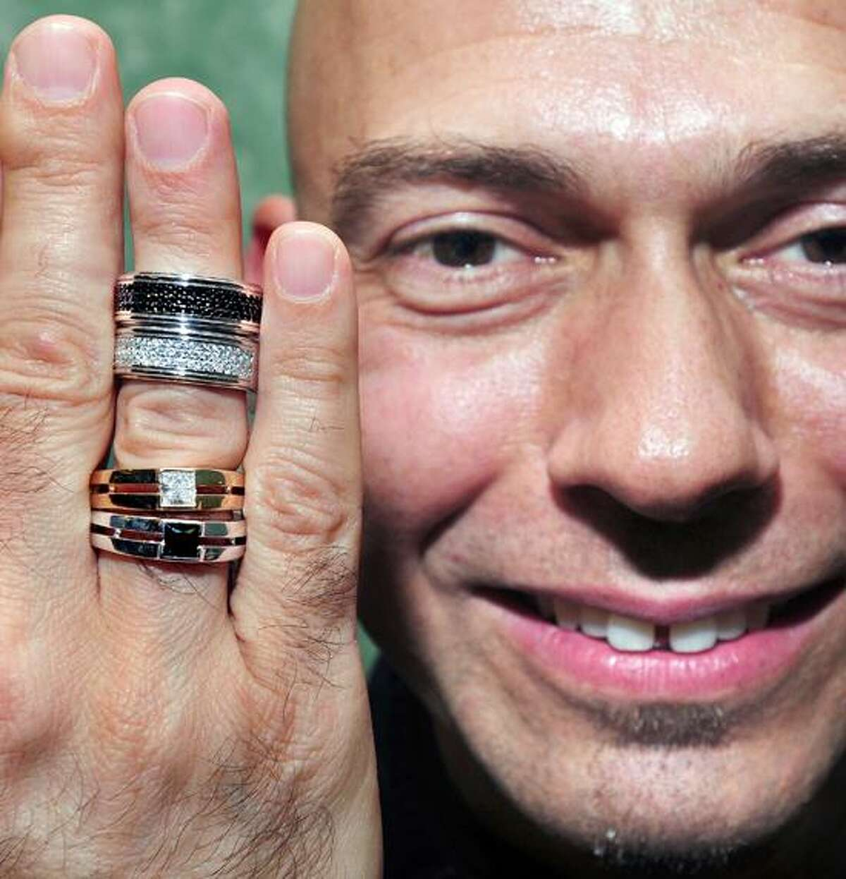 Jewelry designer Rony Tennenbaum shows off a set of pave bands from the LVOE collection (top) and a set of diamond solitaire rings (bottom) at Cellini Jewelers in West Haven. They are designed for same sex couples. Photo by Arnold Gold/New Haven Register