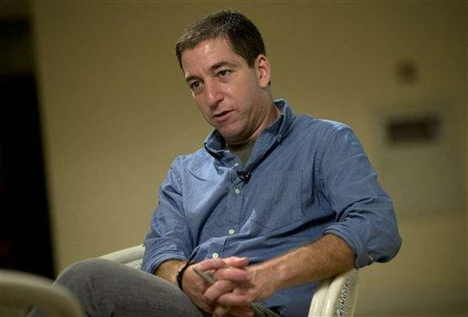 "Journalist Glenn Greenwald speaks during an interview with the Associated Press in Rio de Janeiro, Brazil, Sunday, July 14, 2013.  Greenwald, The Guardian journalist who first reported Edward Snowden's disclosures of U.S. surveillance programs says the former National Security Agency analyst has ""very specific blueprints of how the NSA do what they do.""(AP Photo/Silvia Izquierdo) Photo: AP / AP"