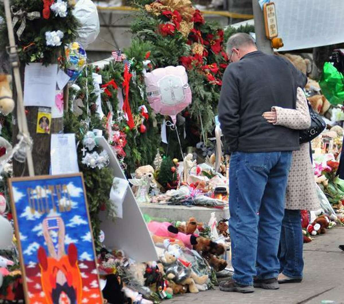 People look over the memorials in the center of Sandy Hook on Dec. 16, 2012. Register file photo