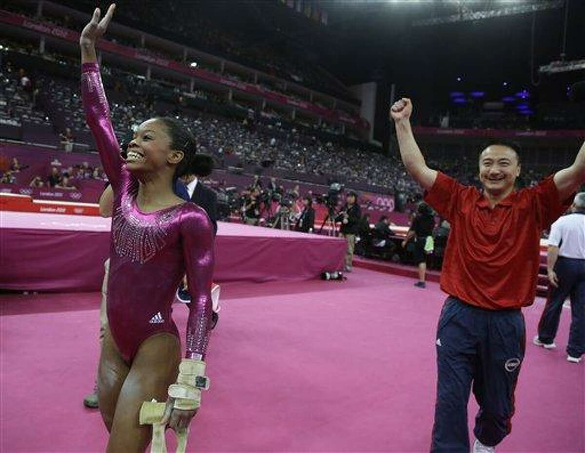 U.S. gymnast Gabrielle Douglas waves to the audience after her final and deciding performance on the floor, followed by coach Liang Chow during the artistic gymnastics women's individual all-around competition at the 2012 Summer Olympics, Thursday, Aug. 2, 2012, in London. (AP Photo/Julie Jacobson)