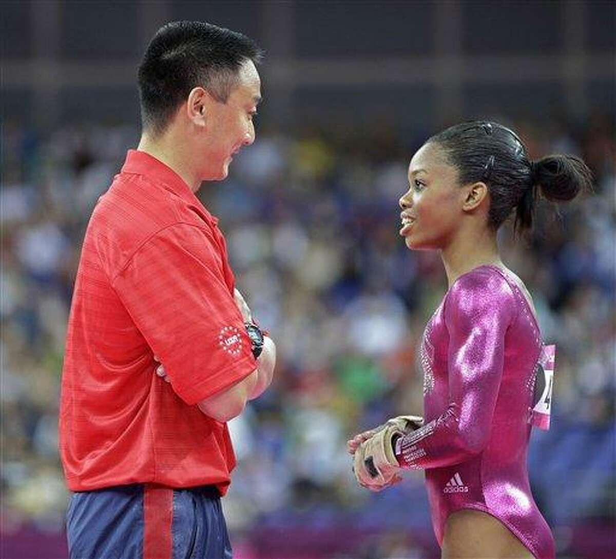 U.S. gymnast Gabrielle Douglas speaks with coach Liang Chow during the artistic gymnastics women's individual all-around competition at the 2012 Summer Olympics, Thursday, Aug. 2, 2012, in London. (AP Photo/Julie Jacobson)