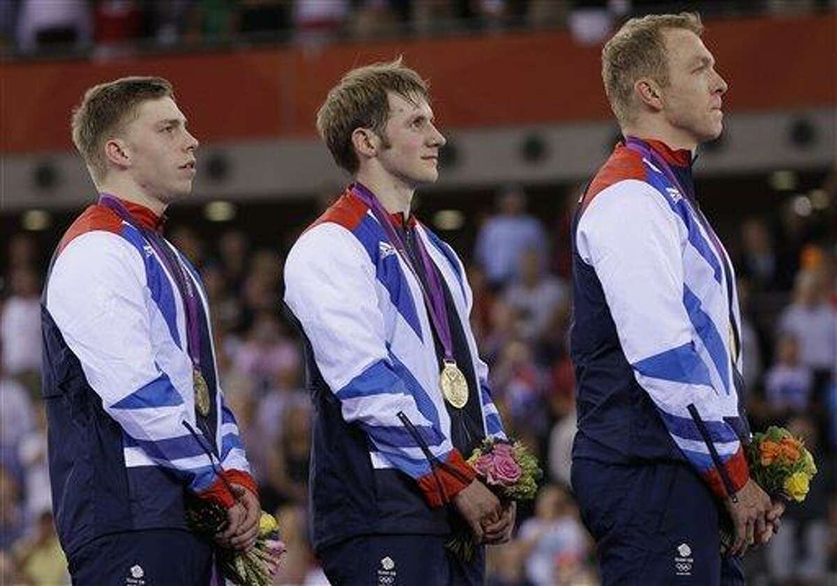 Britain's Chris Hoy, right, Jason Kenny. center, and Philip Hindes, left, show off their gold medals after winning the men's team sprint track cycling event in the velodrome during the 2012 Summer Olympics, Thursday, Aug. 2, 2012, in London. (AP Photo/Matt Rourke)