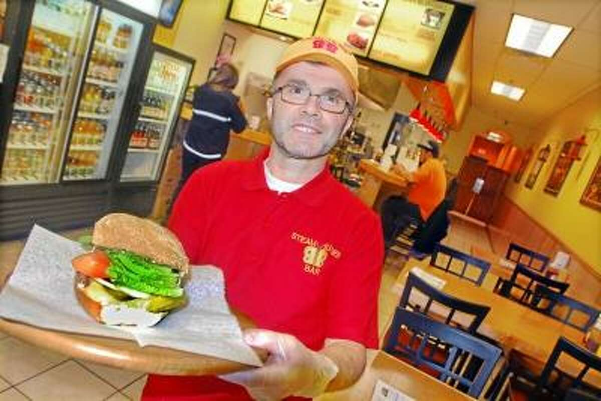 Milford resident Huseyin Aksoy, co-owner of Steamed Burger Bar at 170 Main Street in Middletown with a classic steamed cheeseburger. Aksoy opened the burger bar on September 12, formerly known as K LaMay's Steamed Cheeseburgers. Catherine Avalone/The Middletown Press