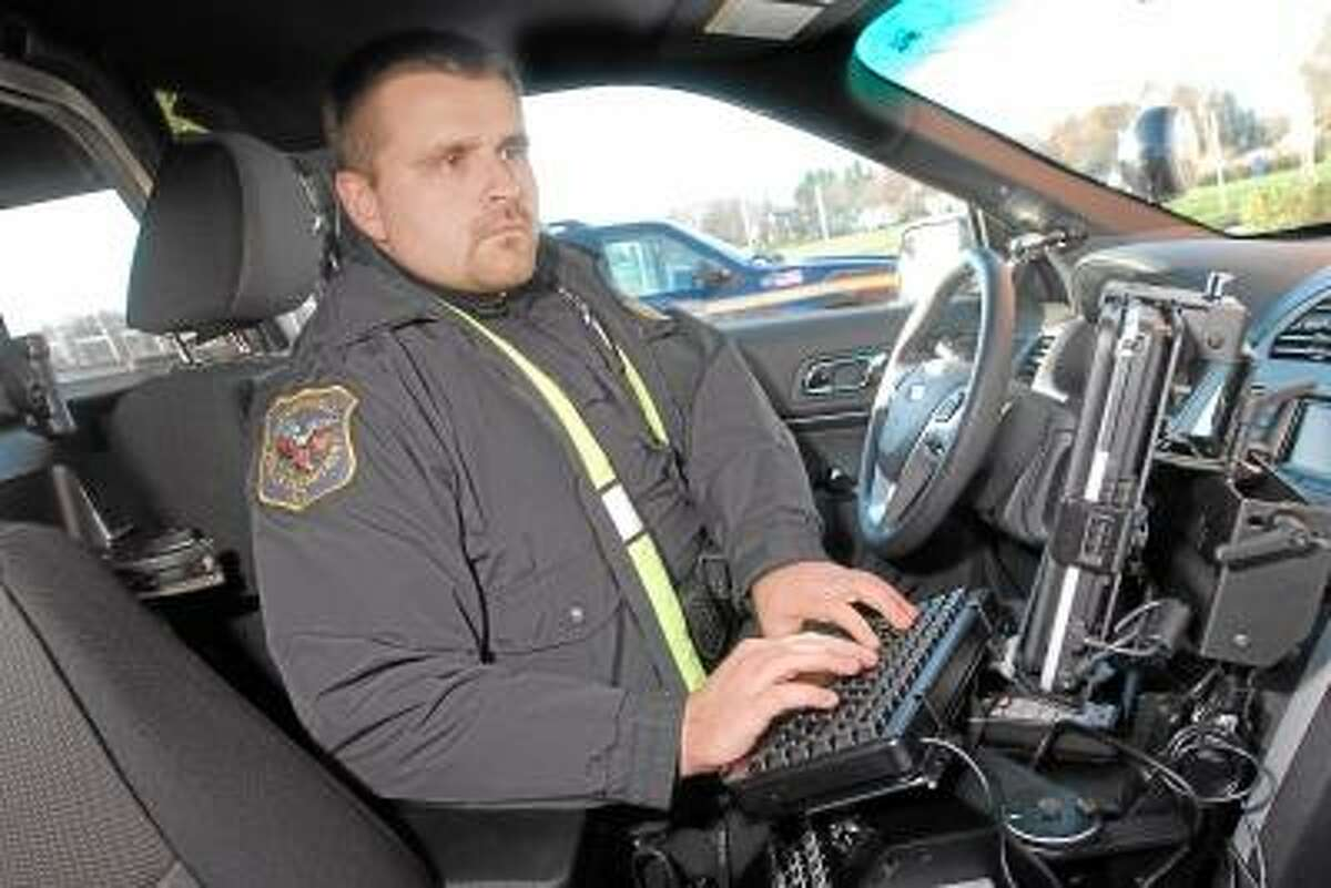 """Catherine Avalone/The Middletown Press Officer Bob Bialko behind the wheel of Cromwell Police Department's new 2013 Ford Explorer sport utility vehicle. Bialko said, """"I's a great addition, with the all wheel drive, we can get to where we need to in inclement weather."""