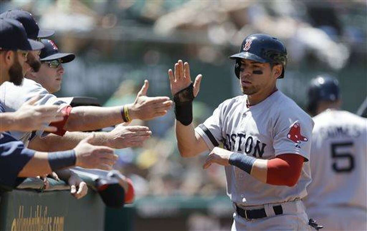 Boston Red Sox's Jacoby Ellsbury, right, is congratulated after scoring against the Oakland Athletics in the sixth inning of a baseball game Sunday, July 14, 2013, in Oakland, Calif. Ellsbury scored on a single by Dustin Pedroia. (AP Photo/Ben Margot)