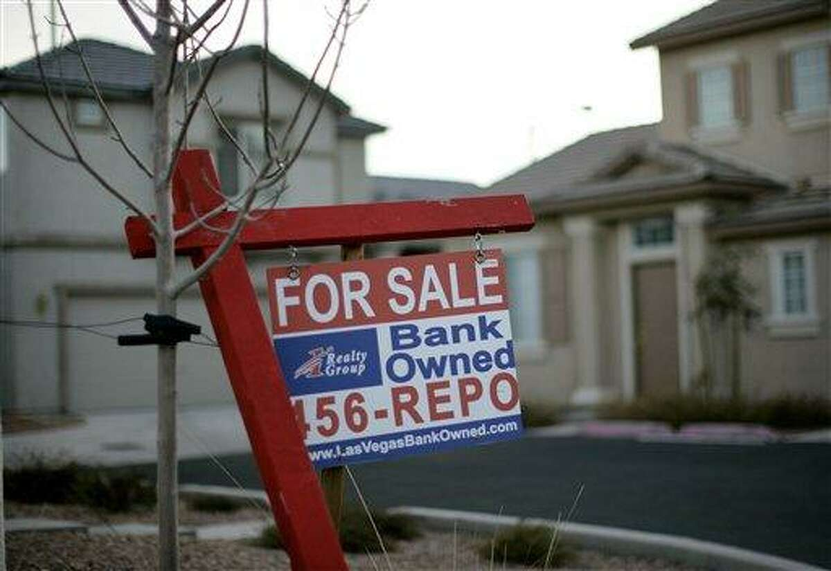 In this 2008 file photo, a for sale sign stands in front of a bank-owned home in Las Vegas. More U.S. homes are entering the foreclosure process, setting the stage for a surge in properties repossessed by lenders in 2012. Thirty-one states posted a monthly increase in homes with a first-time foreclosure notice according to Realty Trac Thursday. Nevada led the pack with an increase of 153 percent. Associated Press