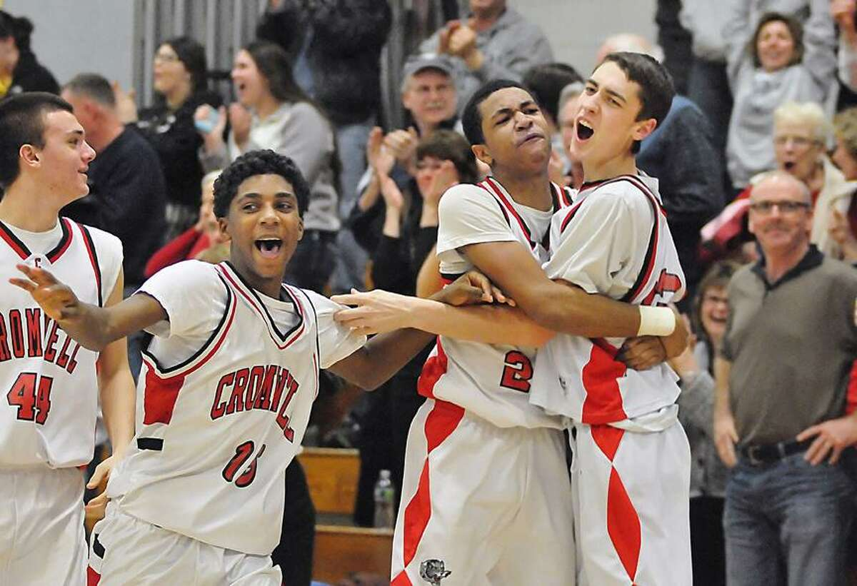 Catherine Avalone/The Middletown Press Cromwell senior forward Kevin Francis (23) at far right celebrates with junior point guard Matt Turkington following Francis' buzzer shot against Immaculate, winning the game 57-55 in Cromwell Monday night in the CIAC First Round State Basketball Tournament.