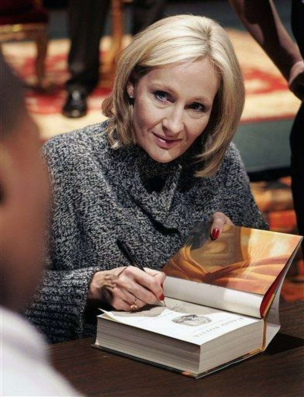 Author J.K. Rowling signing a copy of her book