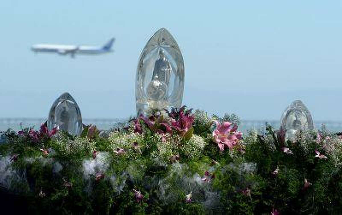 Airplanes have begun to land once again on the newly reopened runway during a prayer ceremony for the Asiana Flight victims put on by the Tzu Chi Foundation in Burlingame, Calif., on Saturday, July 13, 2013.