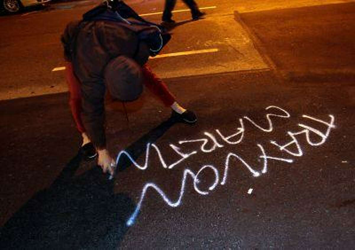 A woman spray paints along Franklin Street during a protest after George Zimmerman was found not guilty in the 2012 shooting death of teenager Trayvon Martin, early Sunday, July 14, 2013, in Oakland, Calif.