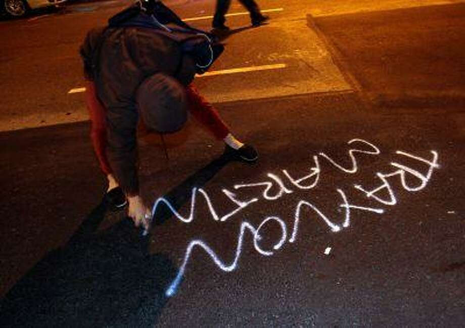 A woman spray paints along Franklin Street during a protest after George Zimmerman was found not guilty in the 2012 shooting death of teenager Trayvon Martin, early Sunday, July 14, 2013, in Oakland, Calif. Photo: ASSOCIATED PRESS / AP2013