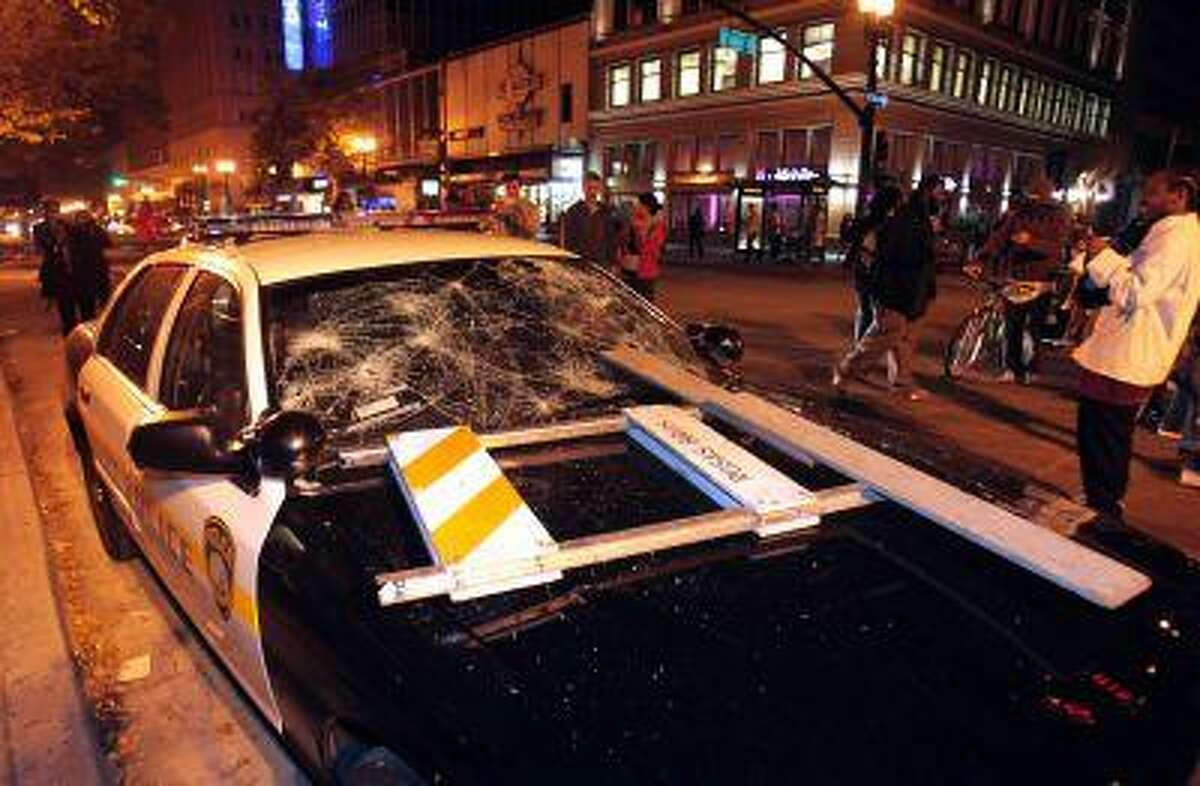 A BART police vehicle is vandalized during a protest after George Zimmerman was found not guilty in the 2012 shooting death of teenager Trayvon Martin, early Sunday, July 14, 2013, in Oakland, Calif.