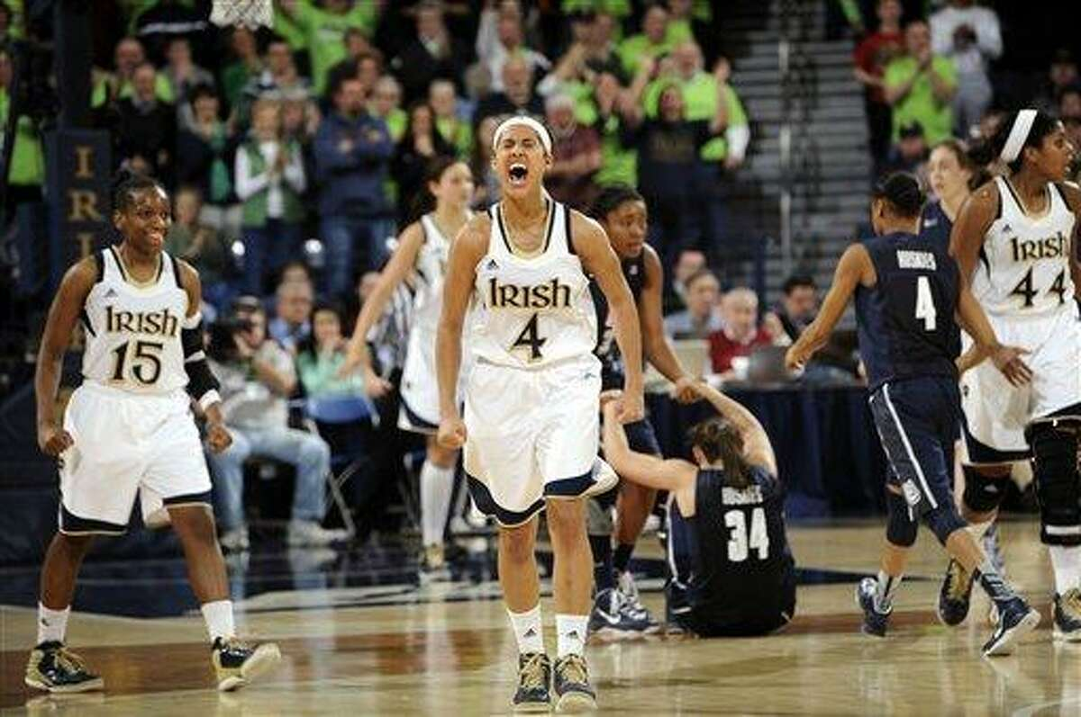 Notre Dame guard Skylar Diggins (4) celebrates a steal and the subsequent Connecticut foul during the third overtime of an NCAA college basketball game, Monday, March 4, 2013, in South Bend, Ind. Diggins scored 29 points as Notre Dame won 96-87 for the Big East regular-season title. Notre Dame guard Kaila Turner (15) also reacts to the play. (AP Photo/Joe Raymond)