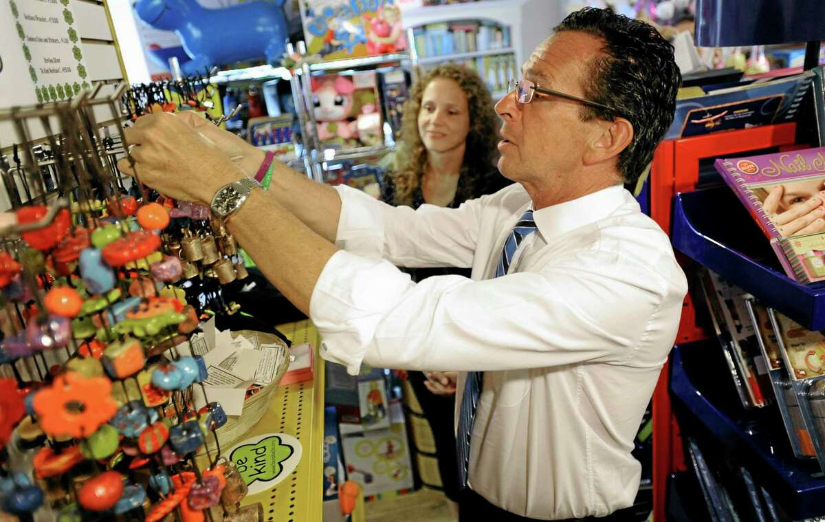 Connecticut Gov. Dannel P. Malloy purchases a bell that encourages kindness from the Ben's Bells organization as toy store owner Tracy Schmid looks on, in the business district of Sandy Hook in Newtown, Conn., Wednesday, July 31, 2013. Malloy is visiting to meet with business owners and talk about economic recovery after the December elementary school shooting that killed 20 students and six adults. (AP Photo/Jessica Hill)