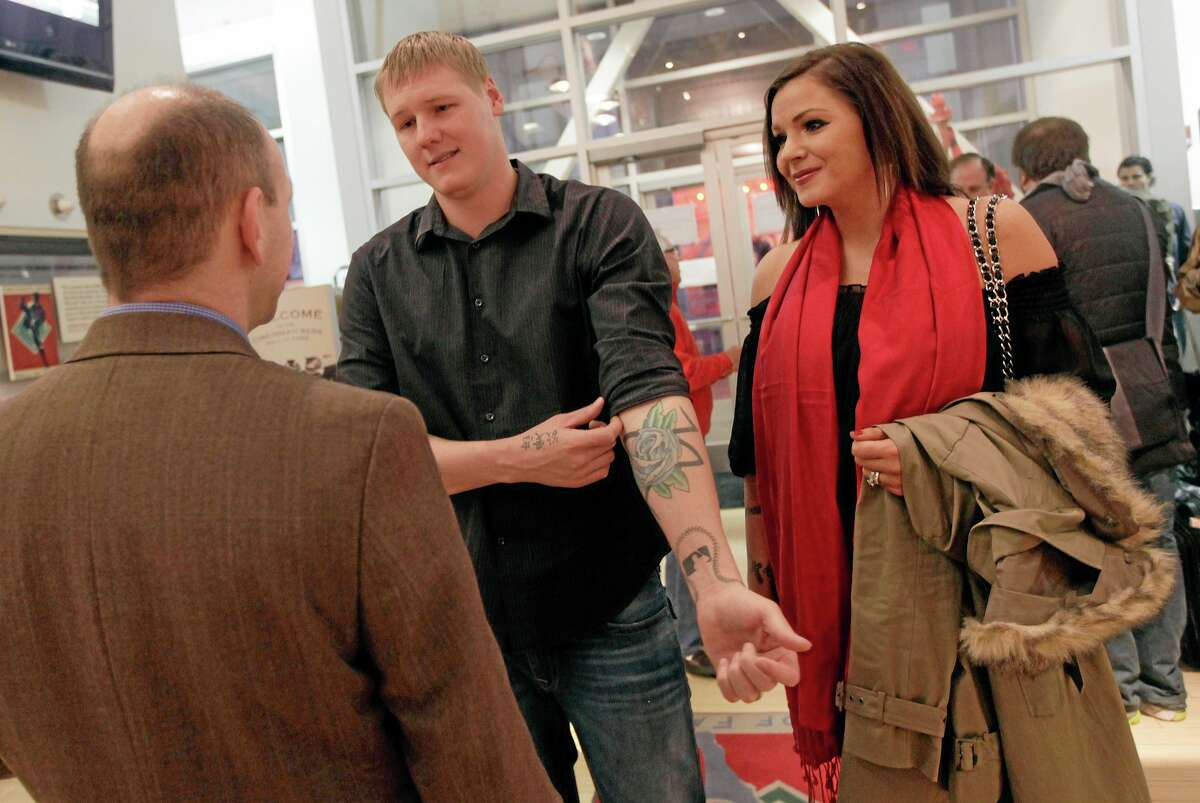 In this photo taken Jan. 26, 2012, Cincinnati Reds pitcher Matt Latos, center, and his wife Dallas, right, tour the Reds museum in Cincinnati. Pittsburgh police are investigating claims by Dallas Latos that she was attacked and had her hair pulled by a fan during the Reds' National League wild card game in Pittsburgh on Tuesday.