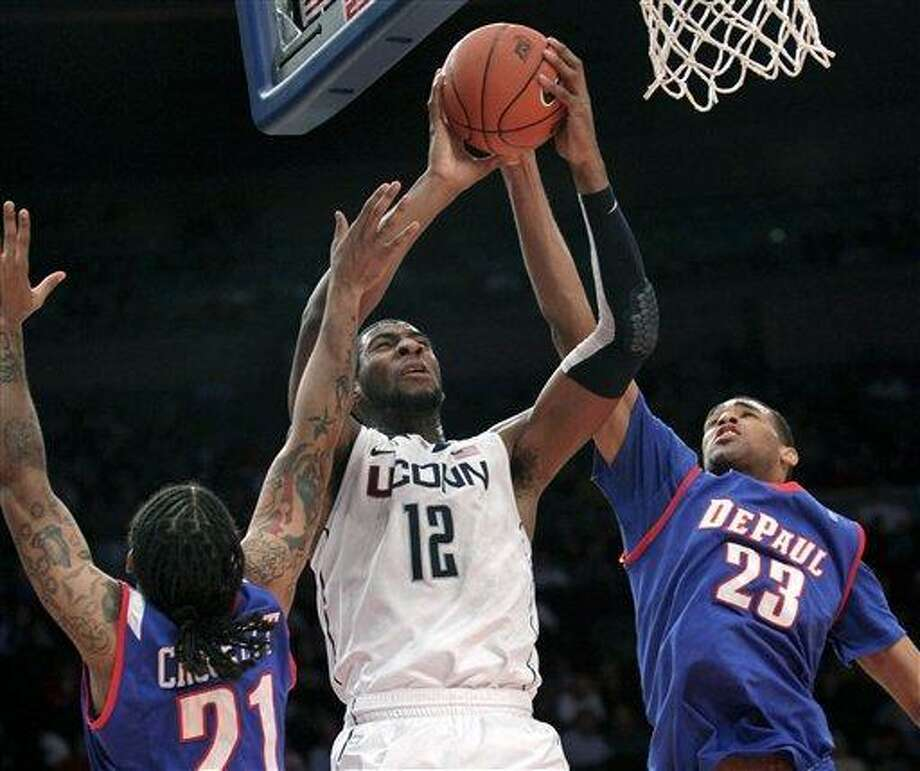 Connecticut's Andre Drummond, center, goes up for a shot past DePaul's Jamee Crockett, left, and Donnavan Kirk during the first round of the Big East NCAA college basketball conference tournament in New York, Tuesday, March 6, 2012.  (AP Photo/Seth Wenig) Photo: ASSOCIATED PRESS / AP2012