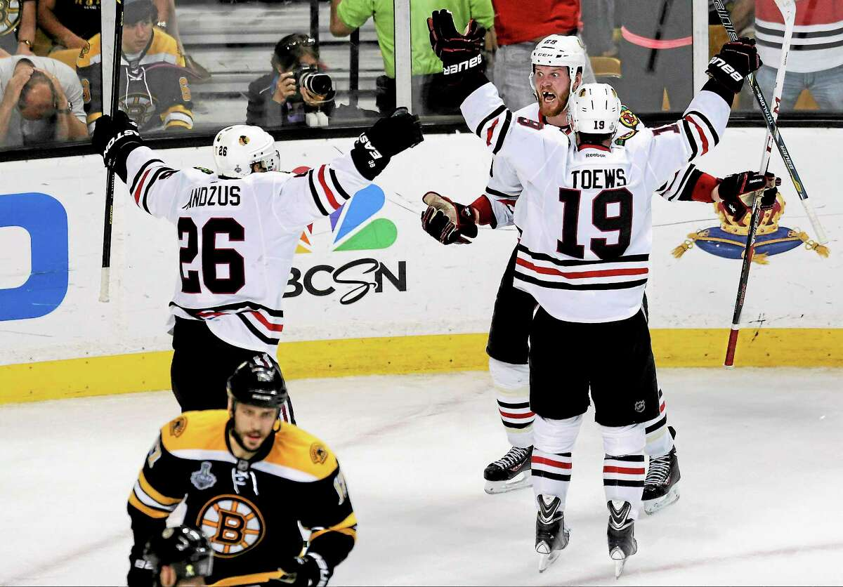 The Chicago Blackhawks' Bryan Bickell, center, celebrates his goal with Jonathan Toews and Michal Handzus during the third period in Game 6 of the Stanley Cup Finals against the Bruins on June 24 in Boston.