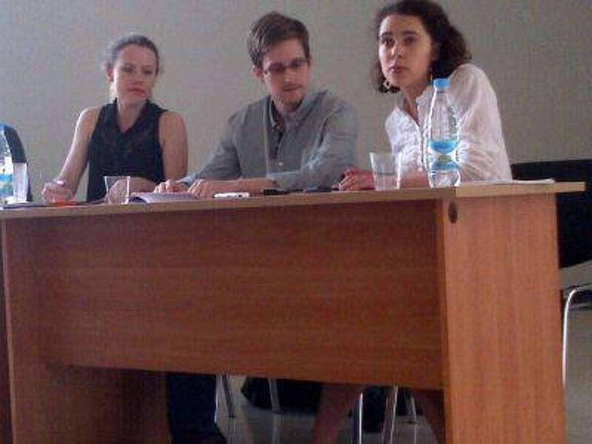 Former intelligence agency contractor Edward Snowden, center, and Sarah Harrison, left, of WikiLeaks speak to human rights representatives in Moscow's Sheremetyevo airport July 12, 2013.